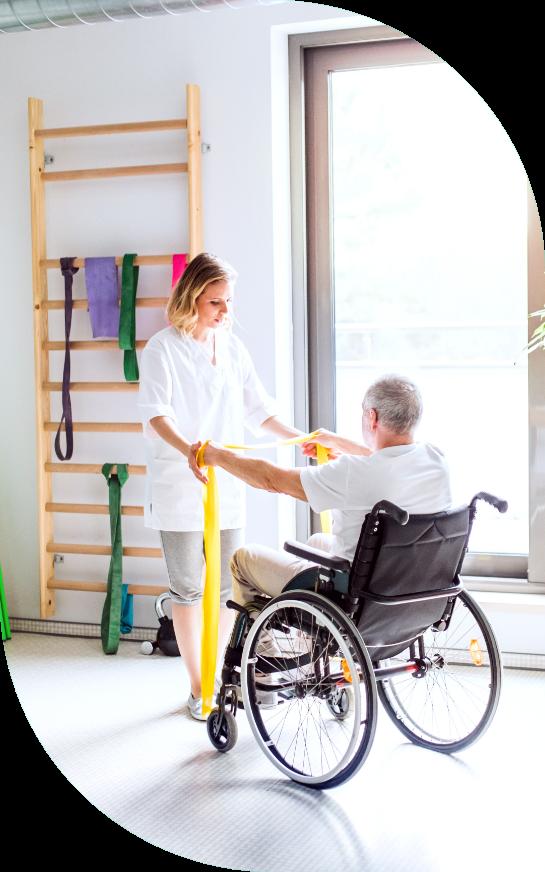 Kuvassa hoitaja kuntouttaa ikäihmistä, joka istuu pyörätuolissa